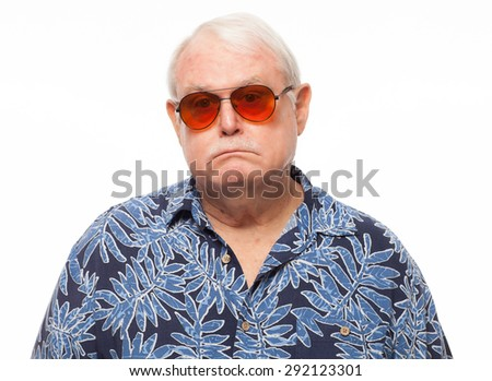Sad retired senior man wearing loud hawaiian shirt on white background. - stock photo