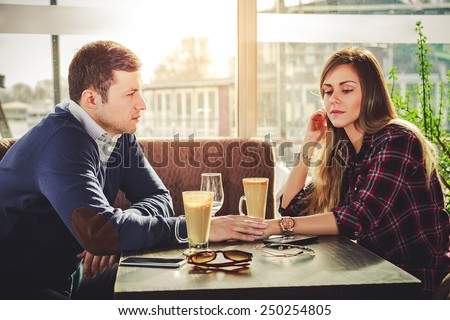 Sad romantic couple holding hands at coffee shop - stock photo