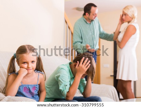 sad russian children in silence while parents arguing at home - stock photo