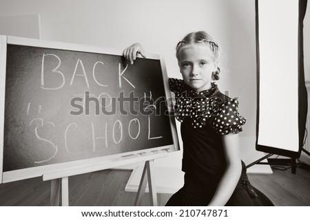 Sad school kid with blackboard - stock photo