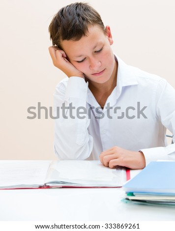 Sad schoolboy at a Desk with notebooks - stock photo