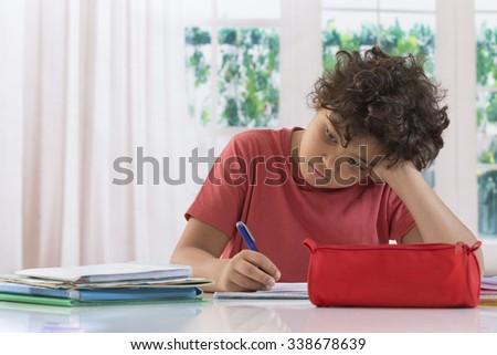 Sad schoolboy doing homework - stock photo