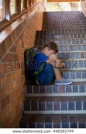 Sad schoolboy sitting alone on staircase at school - stock photo
