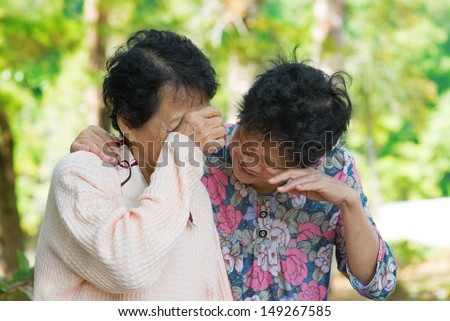 Sad senior Asian women  in grieving the loss of a loved one. Outdoor park. - stock photo