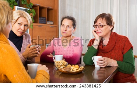 sad senior female friends drinking coffee and sharing problems at table  - stock photo