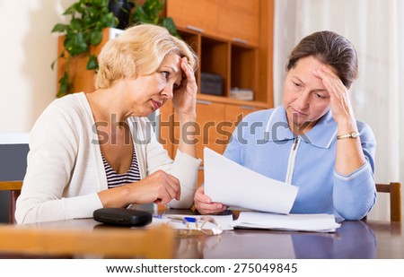 Sad senior ladies checking invoices at office.Focus on the left woman - stock photo