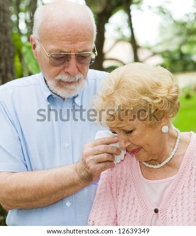 Sad senior lady cries while her husband wipes her tears.  Focus on the woman. - stock photo