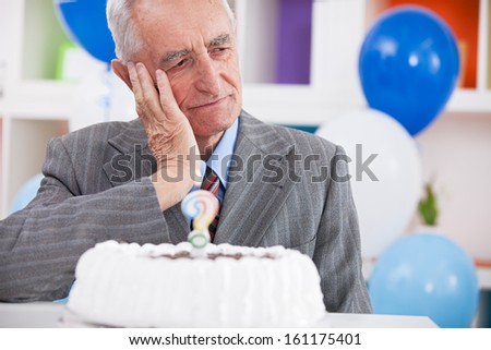 Sad senior man forgot how old is looking at birthday cake with a question mark - stock photo