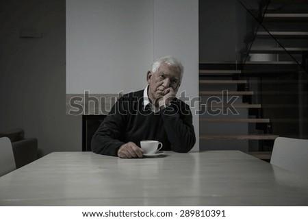 Sad senior man sitting at the table - stock photo