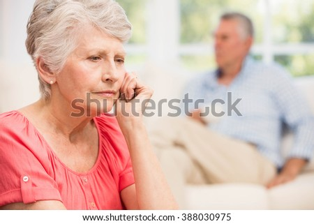 Sad senior woman after arguing with husband in living room - stock photo