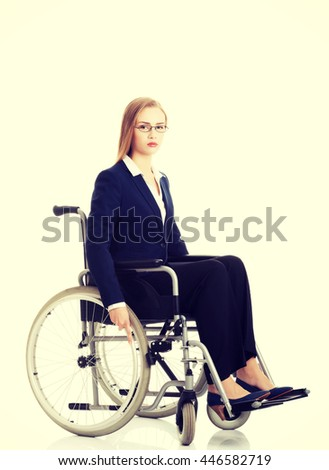 Sad, serious business woman sitting on wheelchair. - stock photo