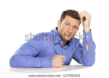 sad, serious man in a blue shirt on white desk - stock photo