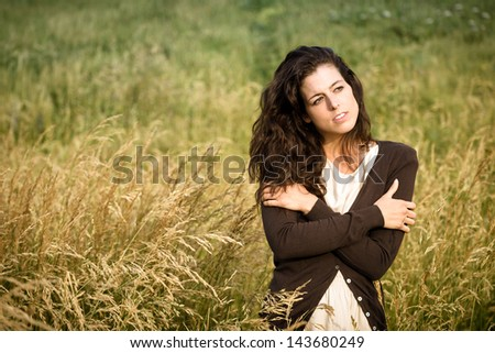 Sad shivery woman in brown sweater jacket hugging herself and walking in nature field on late summer cold day. Sadness, melancholia and heart broken concept.