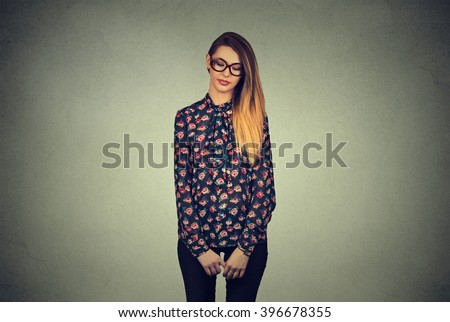 Sad shy insecure young woman in glasses looking down avoiding eye contact standing isolated on gray wall background  - stock photo