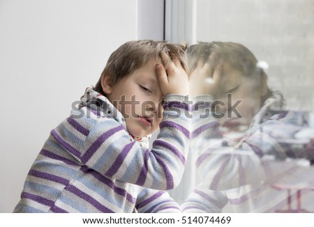 Sad sick child sitting on window