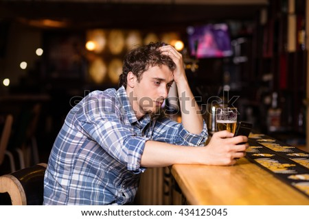sad single man drinking beer at bar or pub, using his cellphone, texting or betting - stock photo