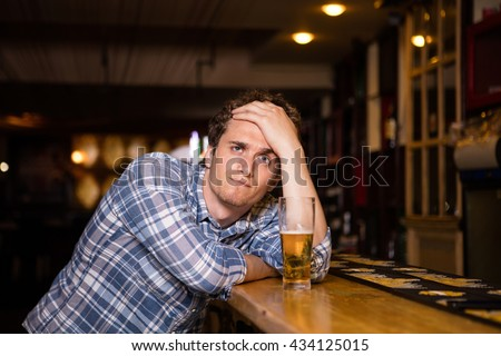 sad single man drinking beer at bar or pub, watching the game