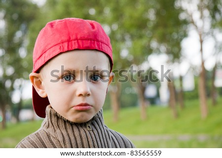 Sad small boy in red cap outdoors - stock photo