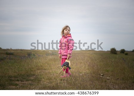 sad small little girl in preschool age standing lonely on yellow rural field and holding soft toy  - stock photo