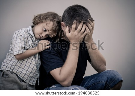 sad son hugging his dad - stock photo