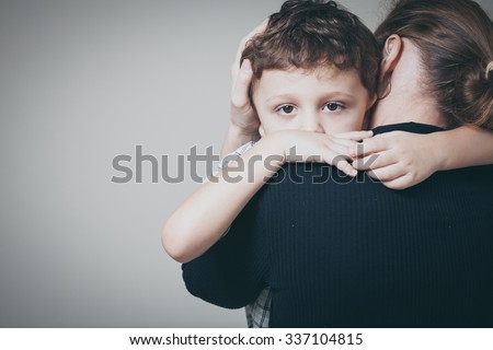 sad son hugging his mother at home. Concept of couple family is in sorrow. - stock photo
