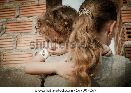 sad son hugging his mother on the background  a brick wall - stock photo
