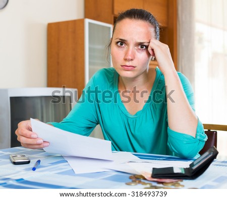 Sad spanish thoughtful girl sits with her bills on the table - stock photo