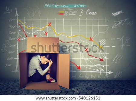 Sad stressed woman sitting inside a box hiding from bad economy financial results