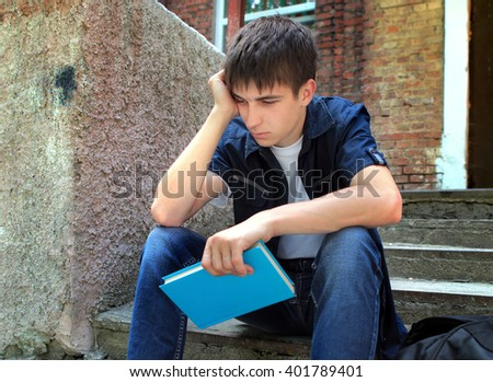 Sad Student with the Book on the Old House Background