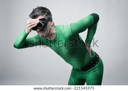 Sad superhero bent over with back pain touching his head and back. - stock photo