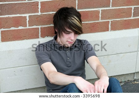 sad teen boy with cool hair sitting outside school