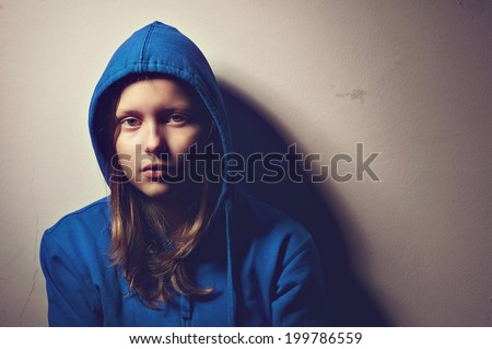 Sad teen girl in hood sitting - stock photo