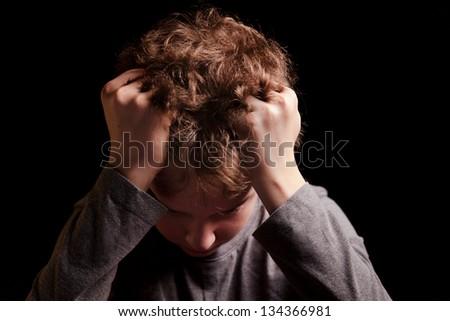 Sad teenage boy on a black background - stock photo