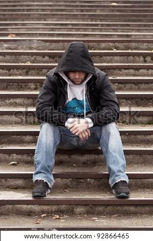 Sad teenage boy with hood sitting on stairs - stock photo