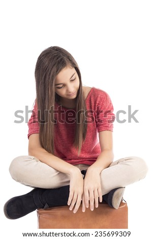 Sad teenage girl looking down over white background - stock photo