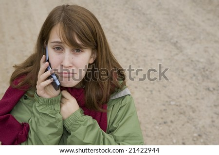 Sad teenage girl on a gravel  road, talking on her cell phone - stock photo