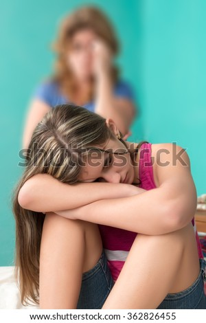 Sad teenage girl sitting on her bed with her worried mother out of focused on the background - stock photo