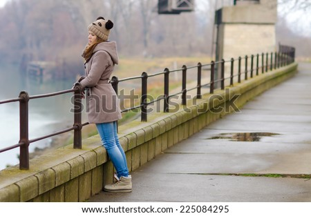 Sad teenage girl standing outside on cold winter day. - stock photo