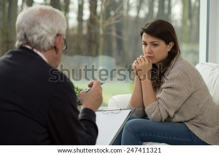 Sad teenage girl talking with her psychologist - stock photo