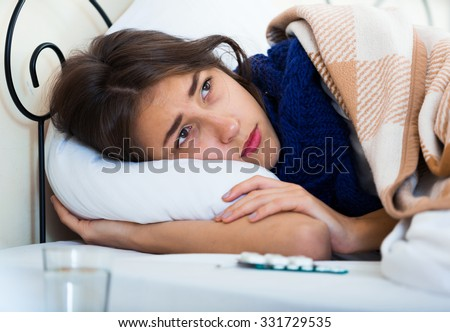 Sad teenage girl with high fever and flu in bed - stock photo