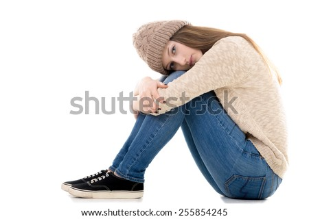 Sad teenage girl with problems sitting with her head on her knees, copy space - stock photo