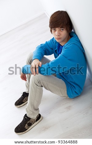 Sad teenager boy sitting on the floor leaning against the wall - stock photo