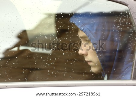 Sad teenager boy worried inside a car looking through the window - stock photo