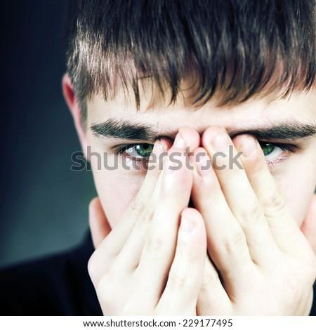 Sad Teenager Face closeup on the Black Background - stock photo