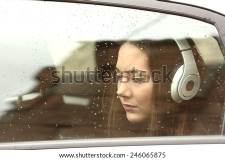 Sad teenager girl inside a car with headphones listening to the music - stock photo