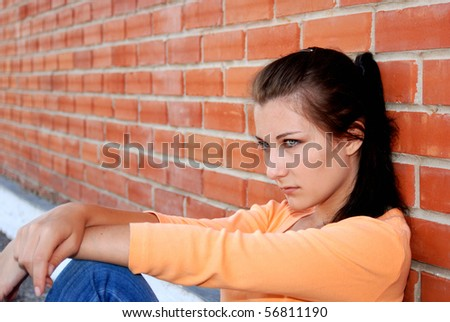 Sad teenager girl sitting by brick wall