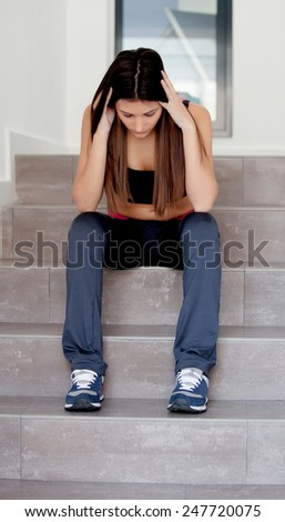 Sad teenager girl sitting on the stairs at home - stock photo