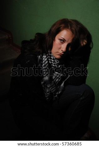 Sad teenager girl sitting on the stone stairs near green wall - stock photo