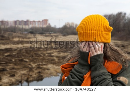 Sad teenager in orange knitted hat and scarf closed her face by hands, stand alone near the scorched field. Spring time - stock photo