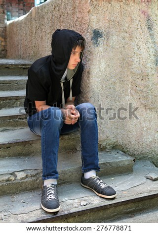 Sad Teenager in the Hood on the landing steps of the Old House